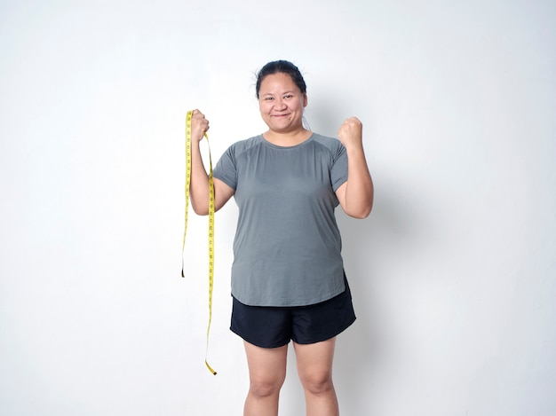 Happy fat woman with measuring tape on white background