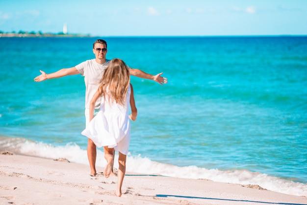 幸せな父と白い砂浜で一緒に楽しんでいる小さな女の子