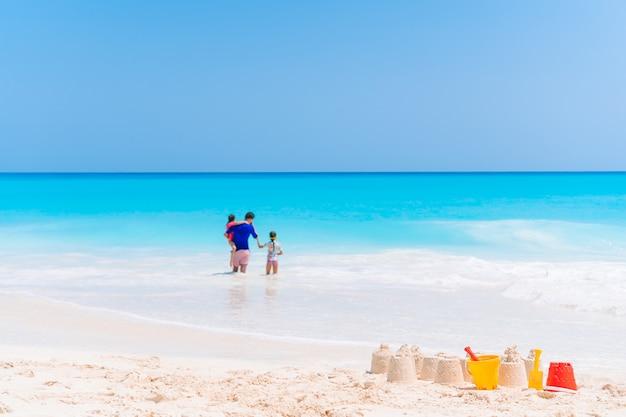 Счастливый отец и очаровательные маленькие дети на тропическом пляже с удовольствием. семейный отдых