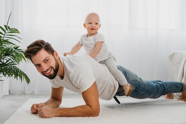 Счастливый отец и ребенок, играя вместе дома