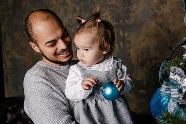 Счастливые отец и дочь украшают елку.