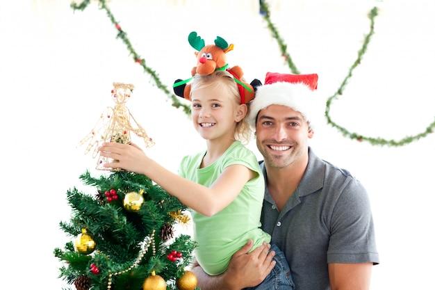Счастливый отец и дочь, украшая вместе елку
