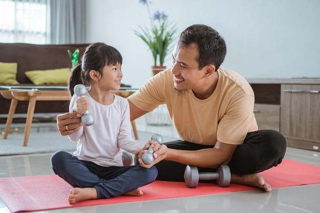 Счастливый отец и дочь тренируются, делая подъем гантелей вместе в гостиной