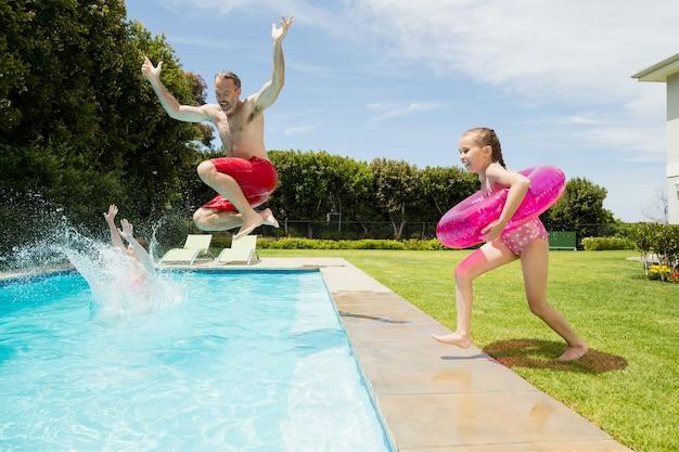 幸せな父と娘がプールでジャンプ