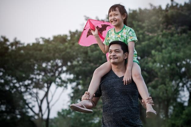 自然の夏に凧と牧草地で幸せな父と娘。父の日の概念