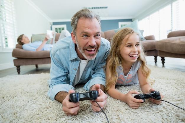 Счастливый отец и дочь играют в видеоигры, лежа на полу в гостиной