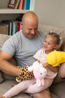 인형을 가지고 노는 행복한 아버지와 딸