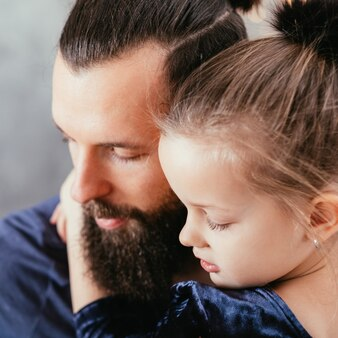 幸せな父と娘の関係。彼女の愛するパパを抱き締めるかわいい女の子のクローズアップの肖像画。