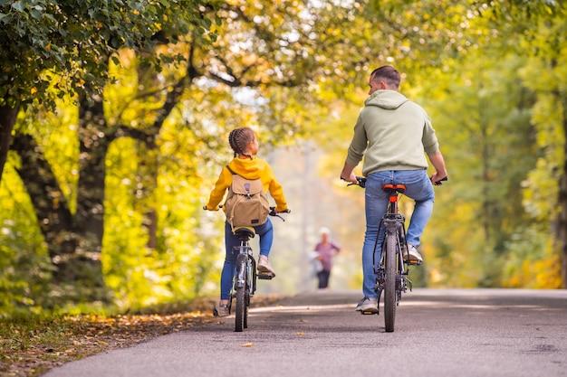 幸せな父と娘は晴れた日に秋の公園で自転車に乗る。