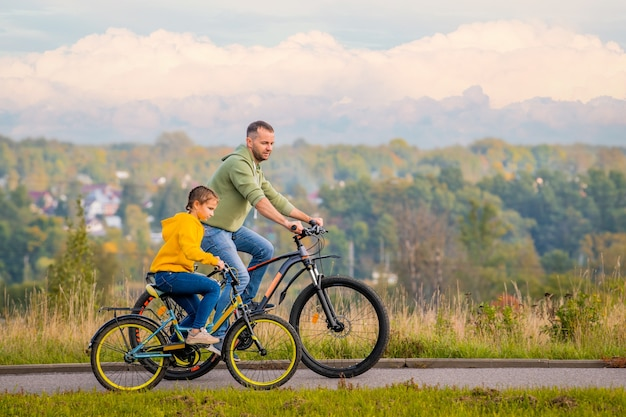 幸せな父と娘は秋に自然の中で自転車に乗る。