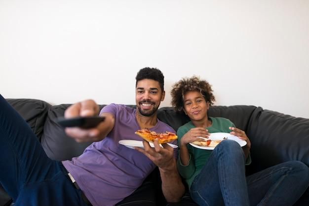 幸せな父と娘がお気に入りのテレビ番組を見て、ピザのスライスを楽しんでいます