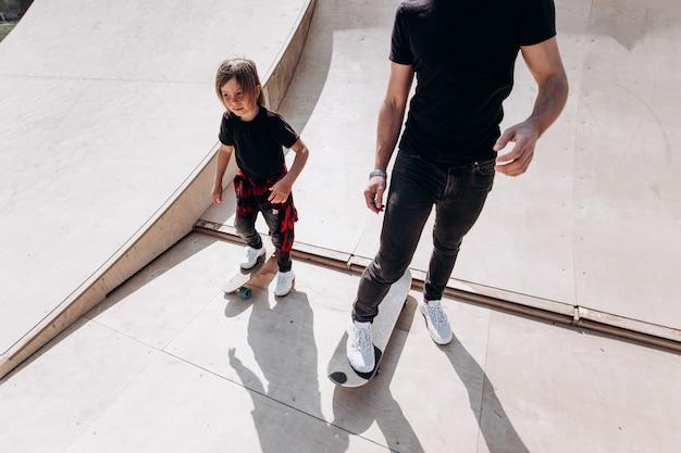 캐주얼한 옷을 입은 행복한 아버지와 그의 어린 아들은 화창한 날 미끄럼틀이 있는 스케이트 공원에서 스케이트보드를 탄다.