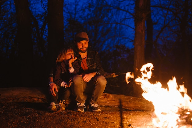 Счастливый отец и его маленький сын сидят вместе на бревнах перед огнем в походе в лесу ночью. .