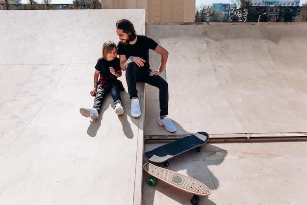 캐주얼한 옷을 입은 행복한 아버지와 아들이 화창한 날 스케이트보드 옆 스케이트장에 있는 미끄럼틀에 앉아 웃고 있습니다.
