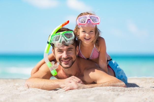 Счастливый отец и его милая маленькая дочь на пляже