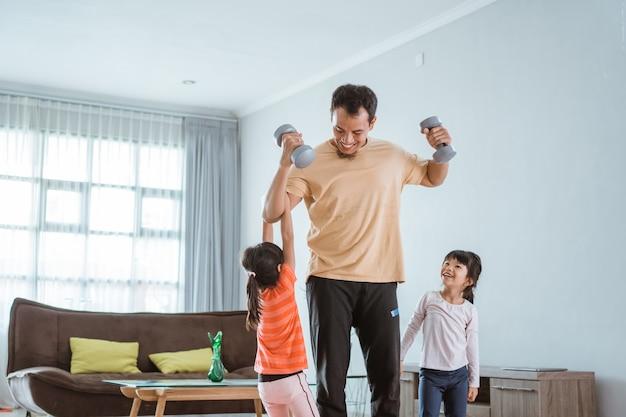 Счастливый отец и ребенок делают упражнения вместе. портрет здоровой семейной тренировки дома. ребенок мешает своему папе во время занятий спортом