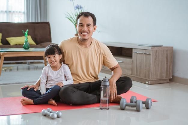 Счастливый отец и ребенок делают упражнения вместе. портрет здоровой семейной тренировки дома. мужчина и его дочь спорт