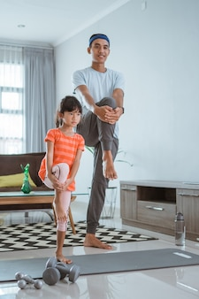 Счастливый отец и ребенок вместе занимаются спортом. портрет здоровой семьи и дочери на растяжке дома