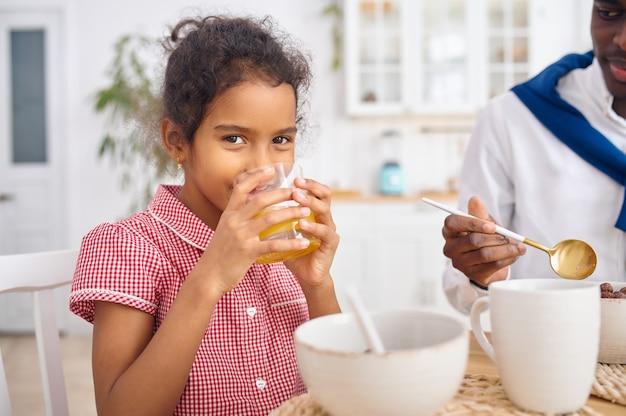 행복한 아버지와 어린 딸은 아침에 주스를 마신다. 웃는 가족은 아침에 부엌에서 먹습니다. 아빠는 여자 아이를 먹여, 좋은 관계