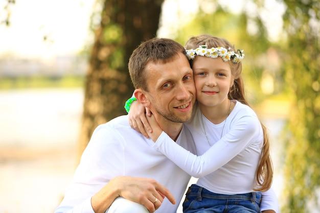 Счастливый отец и маленькая дочь обнимают друг друга в парке