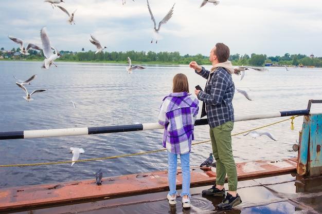 행복한 아버지와 어린 소녀가 갈매기에게 먹이를 준다
