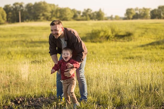 Счастливый отец и маленький сын отдыхают на поле ковыль
