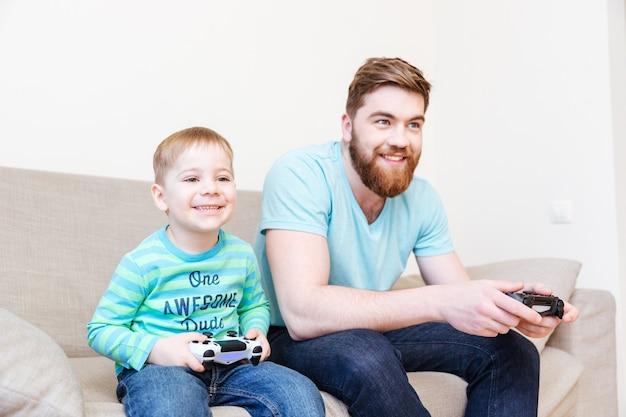幸せな父と幼い息子が座って、自宅のソファでビデオゲームをプレイ