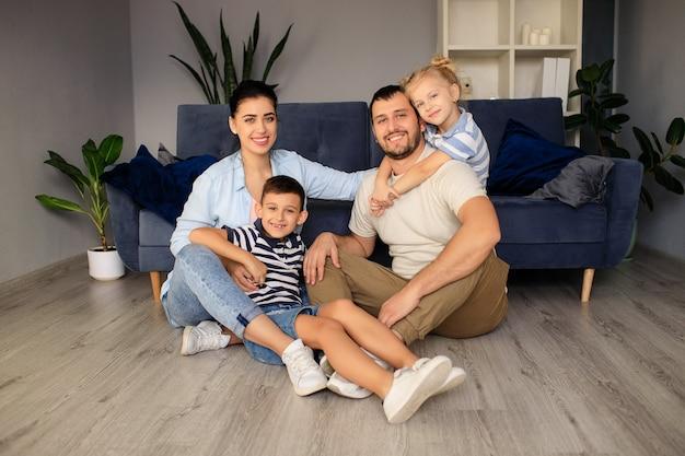 Счастливые отец и мать с маленькими детьми сидят на полу возле дивана и смеются, весело вместе дома в выходные
