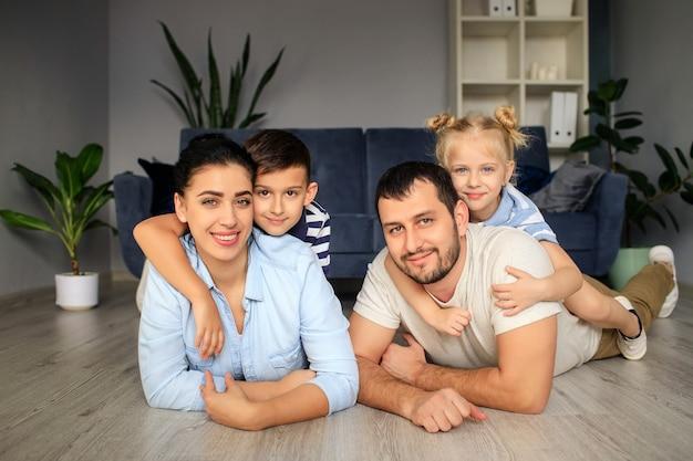 행복한 아버지와 어린 아이들이 소파 근처 바닥에 앉아 주말 동안 집에서 함께 재미를 보면서 웃고있는 어머니
