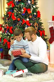 Счастливый отец и сын у елки в гостиной
