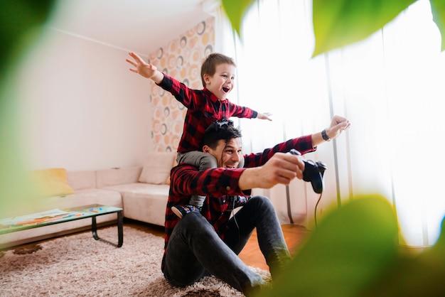 幸せな父と息子がビデオゲームで1位を獲得することを祝っています。息子は父親の上に腕を上げて座っています。
