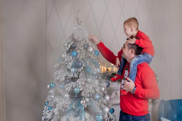 Счастливый отец и сын наслаждаются украшением елки рождественскими шарами и легкой гирляндой, готовясь к празднованию зимних праздников: с рождеством и новым годом 2021 года. концепция семьи.