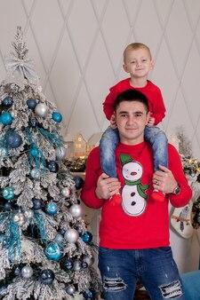 Счастливый отец и сын наслаждаются украшением елки елочными шарами и легкой гирляндой