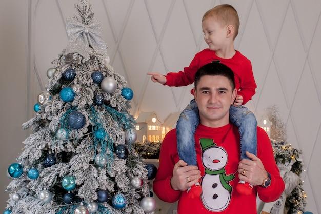 Счастливый отец и сын наслаждаются украшением елки елочными шарами
