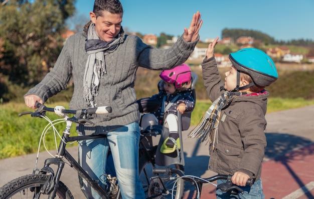 행복한 아버지와 아들은 화창한 겨울날 도시에서 자전거를 타는 법을 배우는 데 성공하여 5개를 줍니다. 가족 레저 야외 개념입니다.