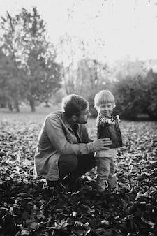 Счастливый отец и сын веселятся в осеннем парке