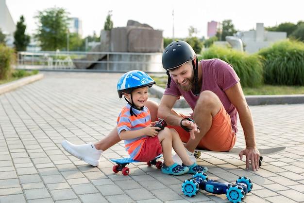 헬멧을 쓴 행복한 아버지와 아들은 스케이트 보드에 앉아 장갑으로 제어되는 로봇 자동차를 가지고 공원에서 놀습니다.
