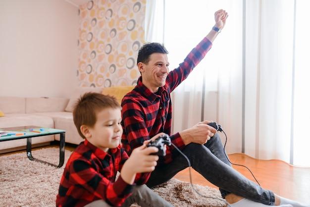 幸せな父と息子が床に座ってビデオゲームをプレイします。どちらもとても興奮しています。父親は息子を獲得しています。