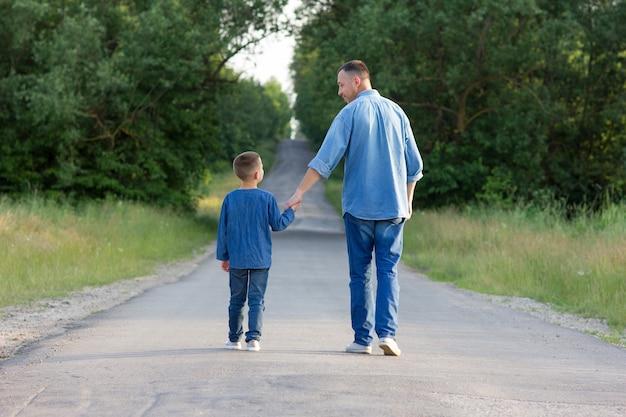 幸せな父と息子が手をつないで道を歩く