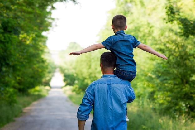 幸せな父と息子が道に沿って歩く