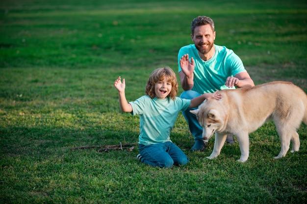 公園の週末の活動で犬と幸せな父と息子幸せな家族のライフスタイルの概念