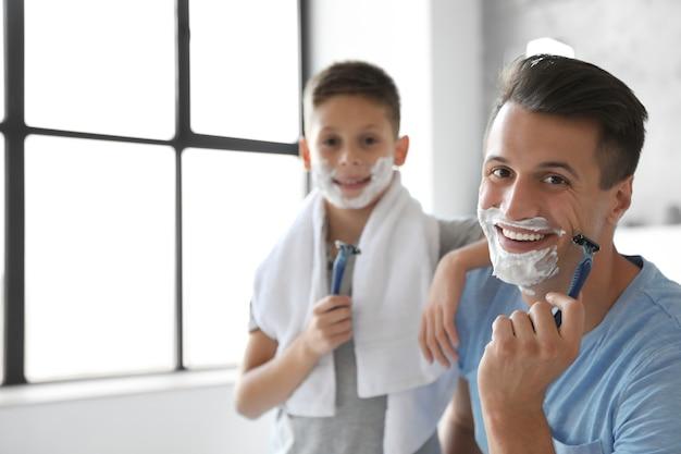 욕실에서 얼굴에 면도 거품을 얹은 행복한 아버지와 아들