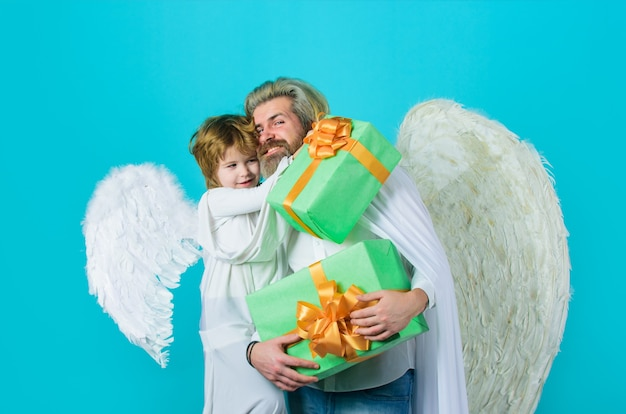 Happy father in angel costume with little son angel holds present cute angel valentines day father
