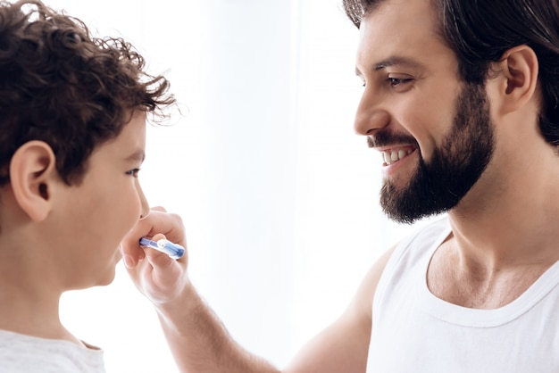 Happy father brushes teeth of young son with toothbrush.