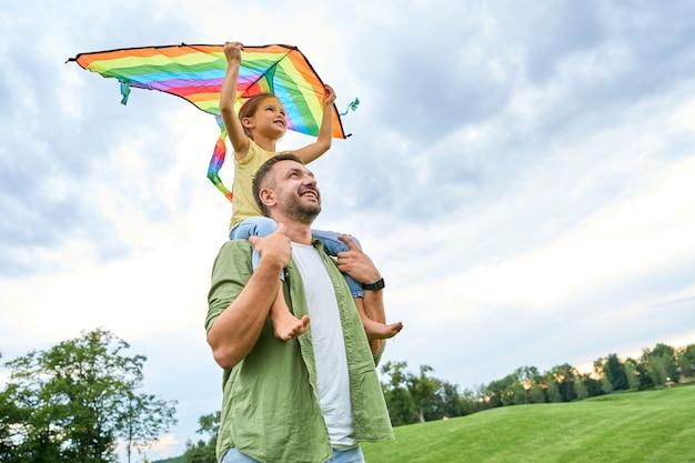 彼女がカラフルな凧を持っている間、彼の肩にかわいい小さな娘を運ぶ幸せな父