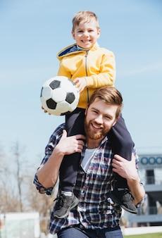 Счастливый отец несет своего маленького сына на плечах