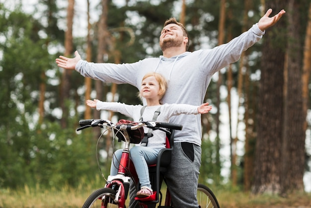 Happy father and daughter on bicycle