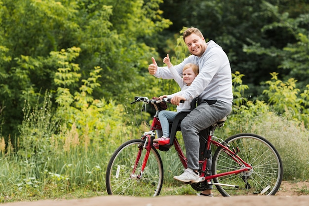 Happy father and daughter on bike