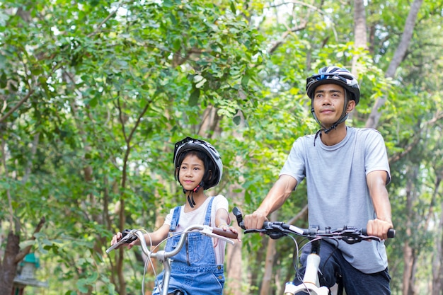 Happy father and daughter cycling in the park