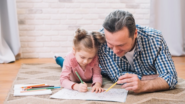 Happy father and daughter drawing together at home